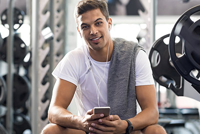 Man in a gym on his phone using an app